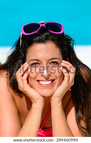 Funny woman with sunscreen lotion in her nose sunbathing and enjoying summer at swimming pool. Sun protection and skin care concept. - stock photo
