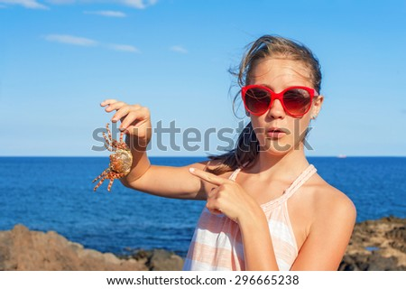 Funny wondering glad teenage girl in red sunglasses holding an atlantic crab on ocean coast. Blue sky background. Multicolored summertime outdoors image. - stock photo