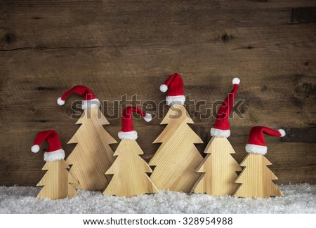 Funny wooden christmas background with trees and santa hats on snow. - stock photo
