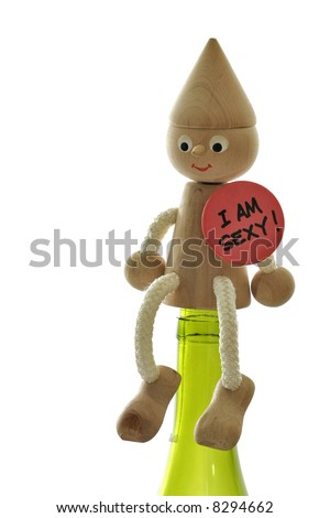 Funny wooden figure sitting on the wine bottle. Isolated on the white background