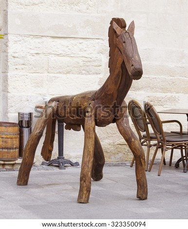 Funny wooden horse near the cafe attracting visitors - stock photo