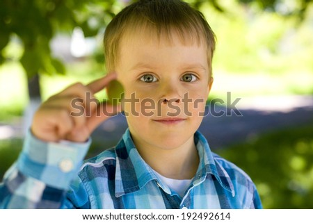 Funny 5 year-old boy shows apricot  - stock photo