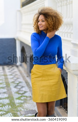 Funny young African American woman, model of fashion, smiling with afro hairstyle and green eyes wearing blue sweater and yellow skirt in urban background