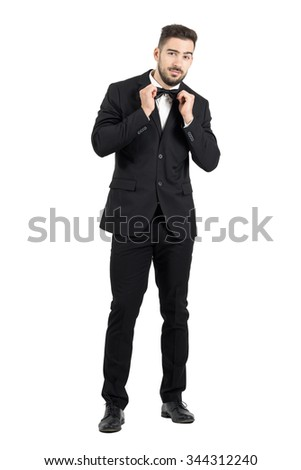 Funny young bearded man adjusting bow tie looking at camera. Full body length portrait isolated over white studio background. - stock photo