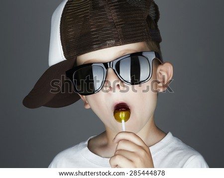 Funny Young Boy Eating A Lollipop.Fashionable child in sunglasses and tracker hat - stock photo