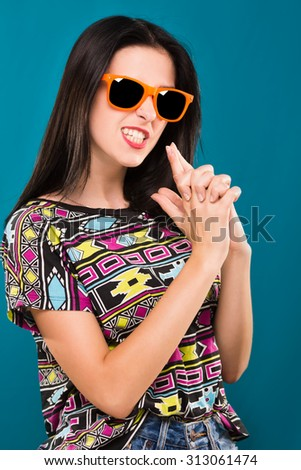Funny young brunette woman, wearing in colorful shirt and orange sunglasses, posing on the blue background, in studio, waist up - stock photo