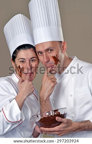 Funny young cook couple tasting chocolate cream. - stock photo