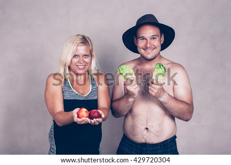 Funny young corpulent couple holding lettuce and nectarine. - stock photo