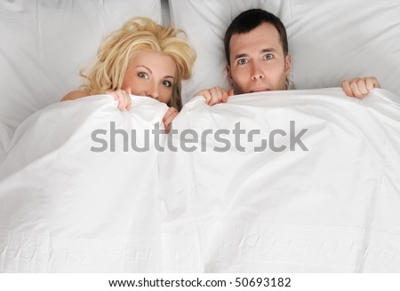 Funny young couple in a bed - stock photo