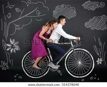 Funny young couple ride the bike, on black background - stock photo