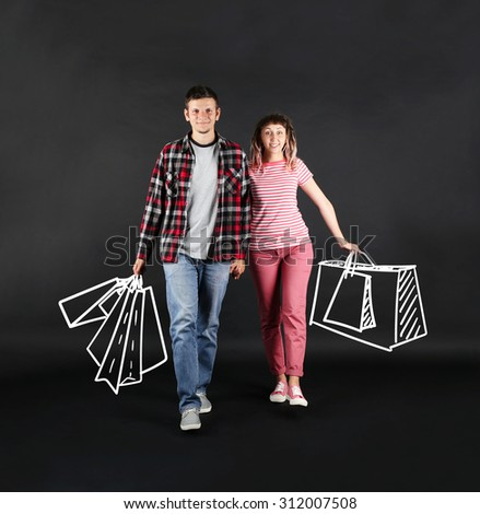 Funny young couple with shopping bags on black background - stock photo