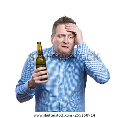 Funny young drunk man holding a beer bottle. Studio shot on white background. - stock photo