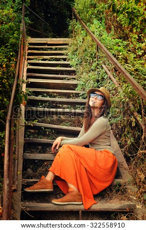 Funny young fashion girl making duck face against the old wooden stairs, outdoor. - stock photo
