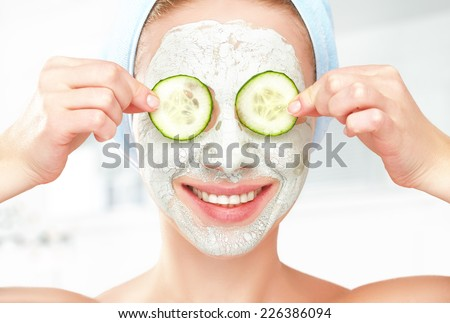 Funny young girl with a mask for skin face and cucumbers on eyes - stock photo