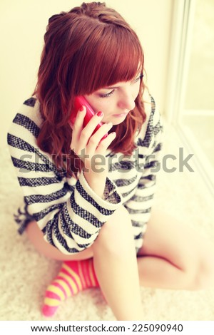 Funny young girl with bangs sitting on the carpet and talking on the phone in his room. Photo toned style Instagram filters. - stock photo