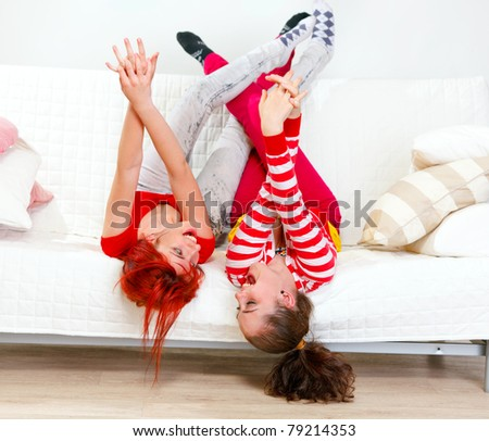 Funny young girlfriends in playful mood lying on sofa with legs raised up - stock photo