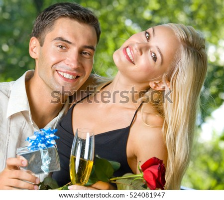 Funny young happy couple with gift and rosa, outdoors. Love, flirt, romantic, relations, celebration theme concept.