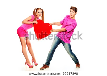Funny young love couple posing together with red heart. Isolated over white background.