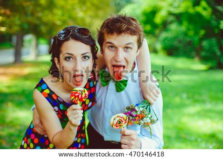 Funny young man and woman show their red tongues after eating sugar candies