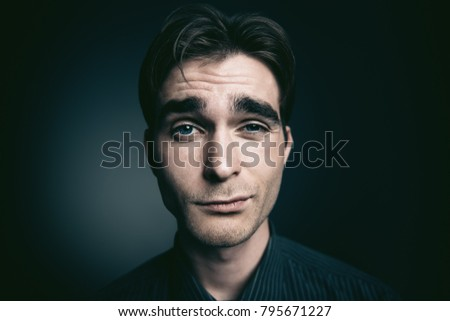 Funny young man looking at camera. Close-up portrait.