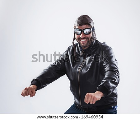 Funny young man, posing as a motorcyclist, is wearing black leather jacket, vintage cap and glasses - isolated on white