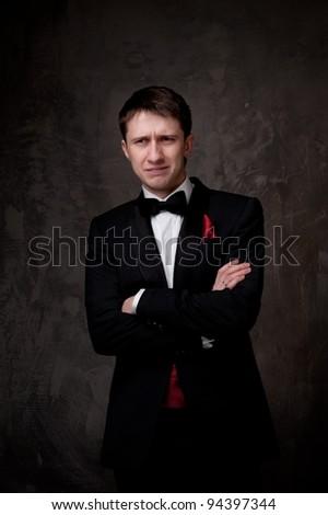 Funny young man wearing tuxedo. - stock photo