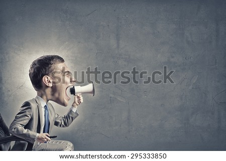 Funny young man with big head screaming emotionally in megaphone - stock photo