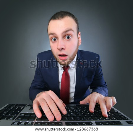funny young man with computer - stock photo