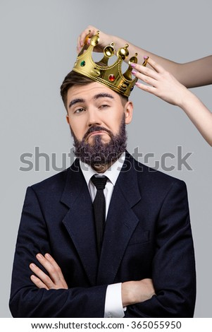 Funny young man, with violet beard and eyebrows, wearing in dark blue suit and tie, posing when girls hands holding crown on his head and smiling, on white background, in studio, waist up - stock photo