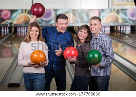 Funny young people smiling at the camera playing bowling