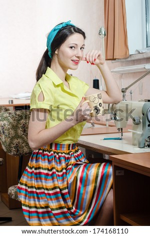 Funny young pinup woman with sewing machine and cup of tea