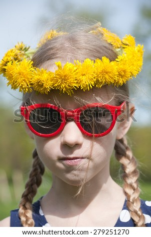 funny young pretty caucasian girl face in yellow dandelions garland on the head and red sunglasses - stock photo