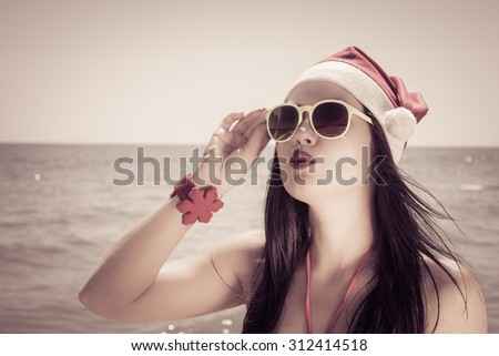 Funny young woman  in Santa Claus hat and sunglasses on a beach. Retro style toned effect