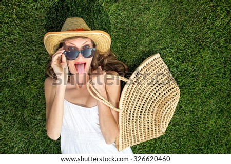 Funny young woman lying on green grass and dreaming. copy space, view from above, soft - stock photo