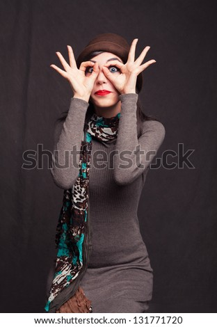 funny young woman making her hands look like glasses on grunge background