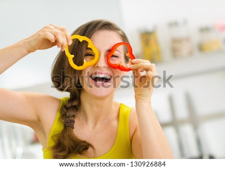 Funny young woman showing slices of bell pepper - stock photo