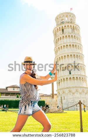 Funny young woman supporting leaning tower of pisa, tuscany, italy - stock photo