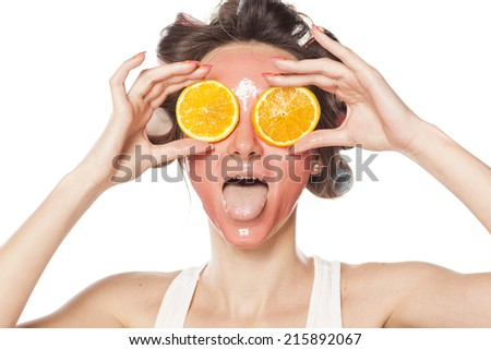 funny young woman with a mask and curlers holding a piece of orange on the eyes