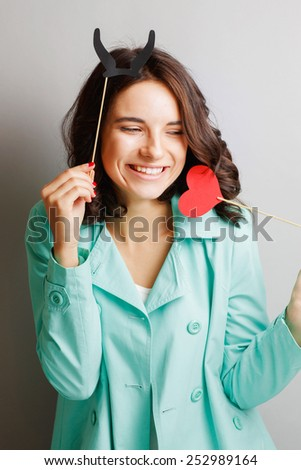 Funny young woman with horns holding a heart. - stock photo