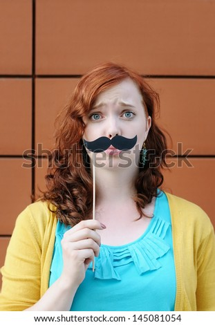 Funny young woman with mustache party accessory - stock photo