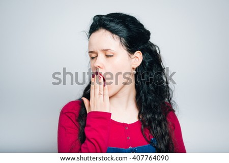 funny young woman yawns, dressed in a overalls, close-up isolated on a gray background - stock photo
