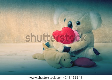 Fur bear and dog toy on wood grunge with love hearts - stock photo