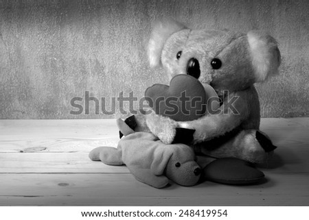 Fur bear and dog toy on wood grunge with love hearts black and white version - stock photo