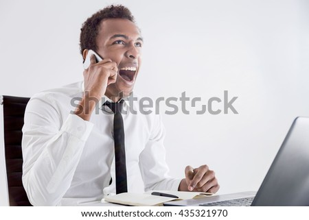 Furious african american businessperson sitting at office desk with laptop raising voice at interlocutor over the phone. Concept of stress and authority abuse - stock photo