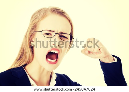 Furious angry business woman trying to punch you. - stock photo