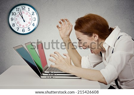 Furious, angry businesswoman screaming at computer, pissed off has nervous breakdown can't take it anymore isolated grey wall background. Negative human emotion face expression feeling life perception - stock photo