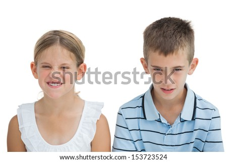 Furious brother and sister posing together on white background - stock photo