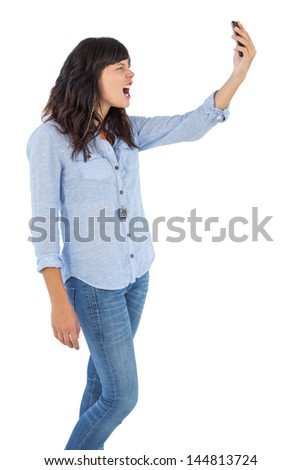 Furious brunette holding her mobile phone and screaming on white background - stock photo