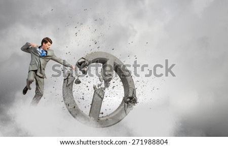 Furious businessman crashing with fist prohibition stone sign - stock photo