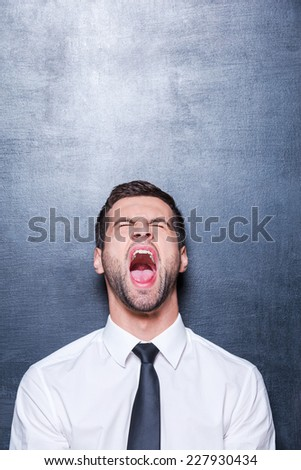 Furious businessman. Furious young man in shirt and tie screaming and keeping eyes closed while standing against blackboard - stock photo